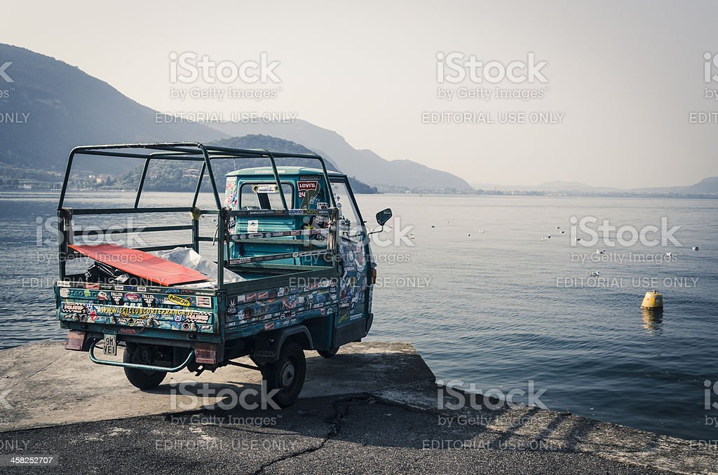 Piaggio Ape covered with stickers and watching lake stock photo