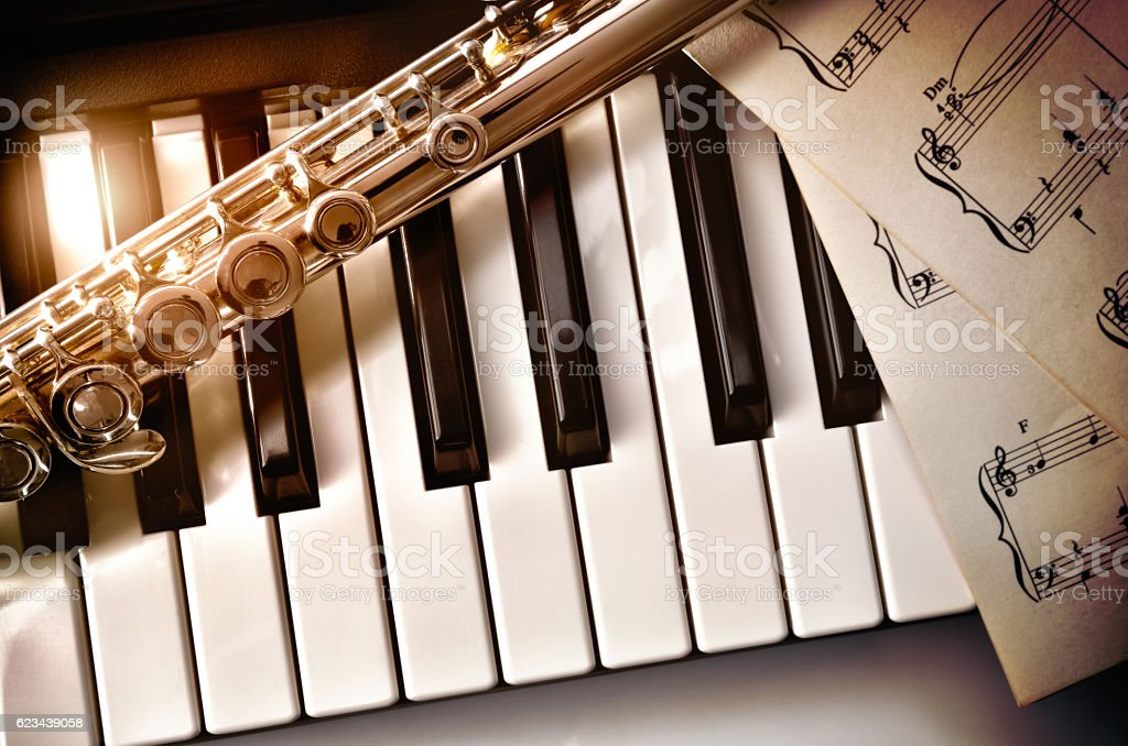 Piano and flute with golden shine and sheet music top stock photo
