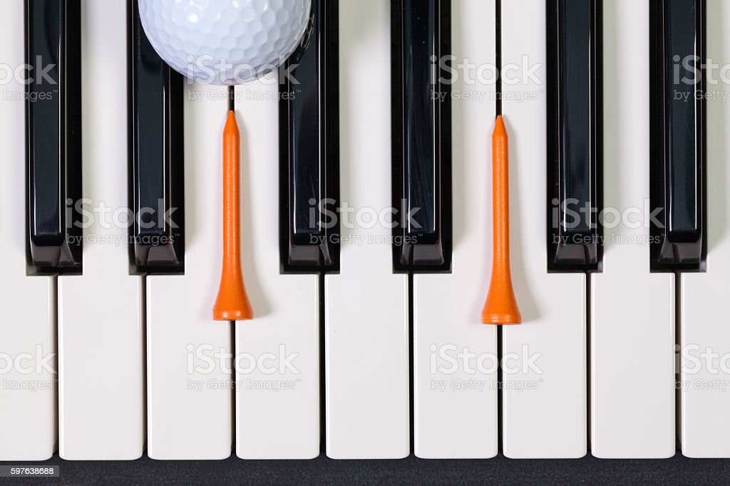 Piano keyboard and different golf balls and tees stock photo