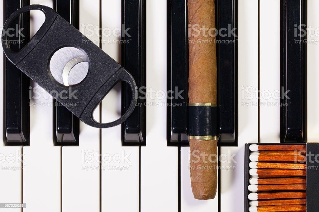 Piano keyboard and luxury cigar stock photo