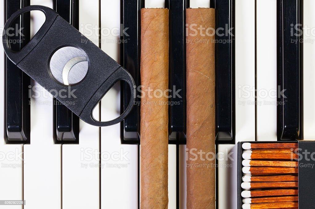 Piano keyboard and luxury cigars stock photo