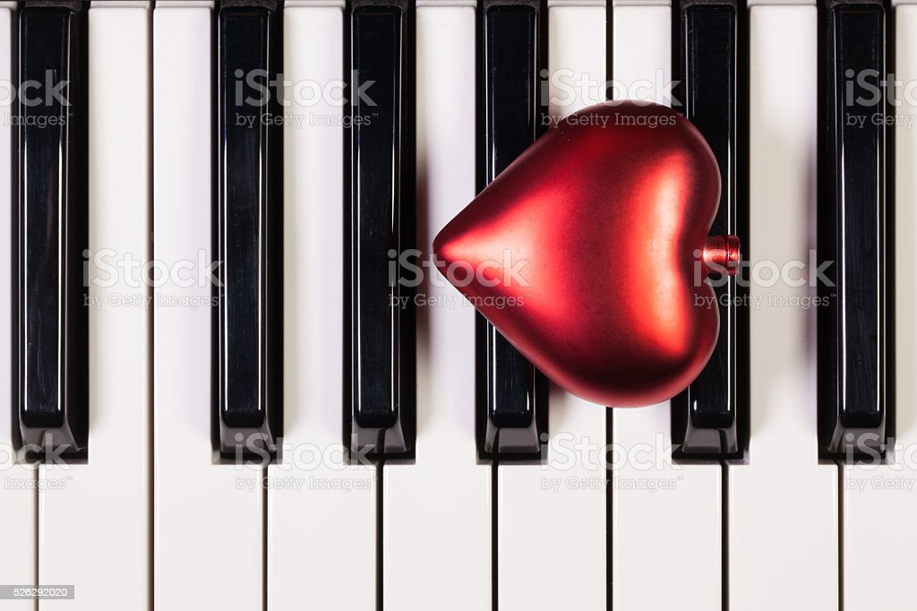 Piano keyboard and red heart stock photo