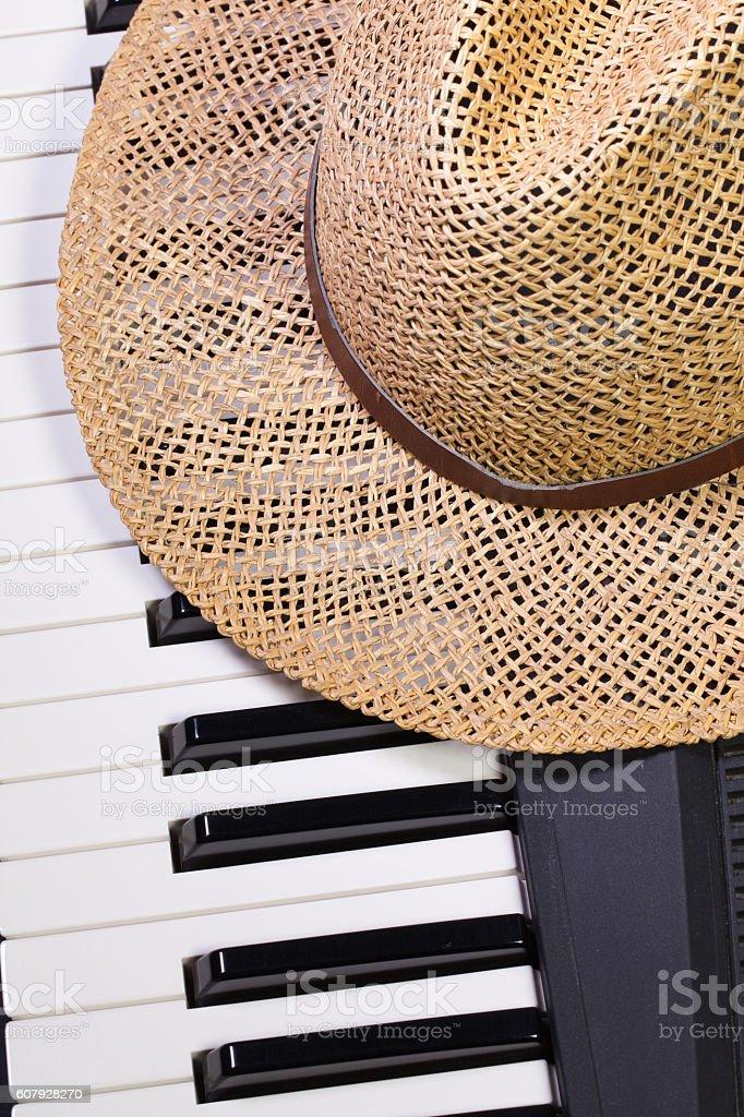 Piano keyboard and straw hat stock photo