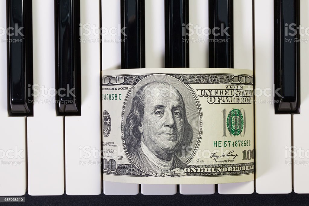 Piano keyboard and US dollar banknote stock photo