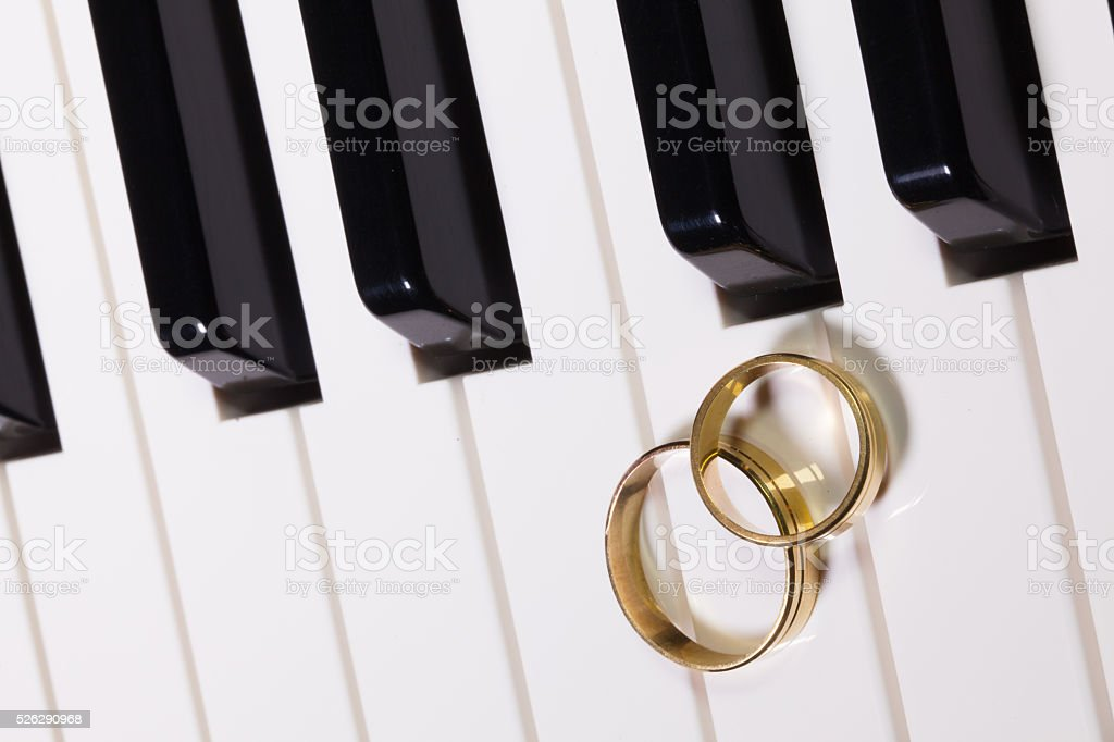 Piano keyboard and wedding rings stock photo