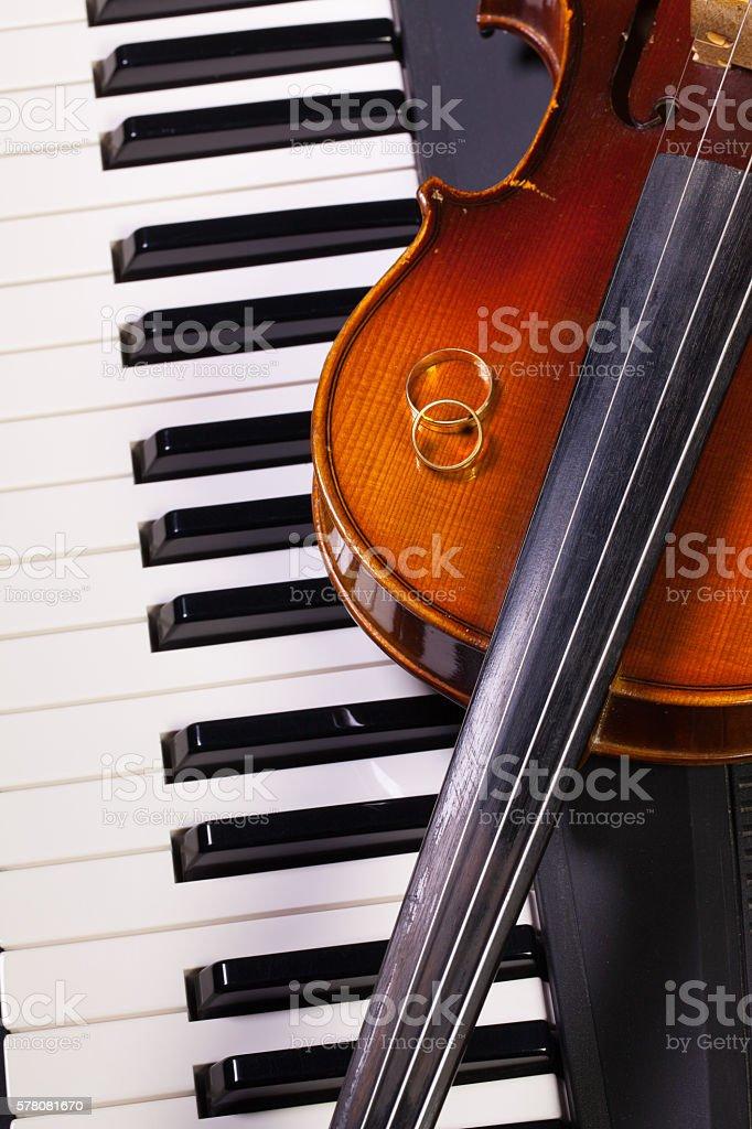 Piano keyboard, old violin and wedding rings stock photo