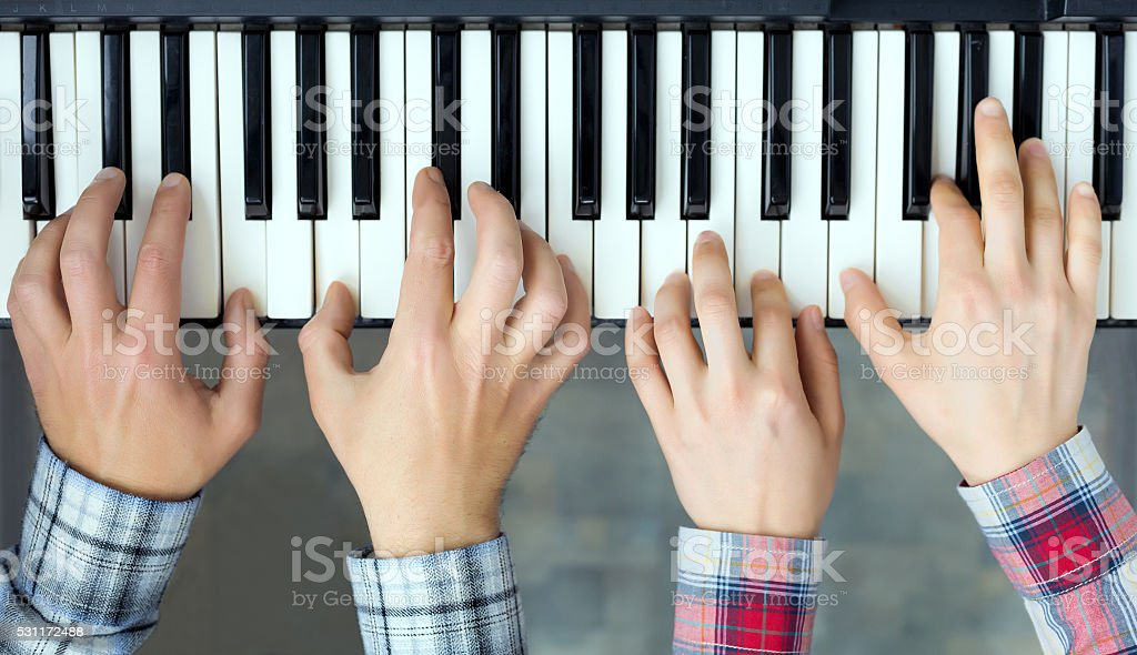 Piano Keyboard top View Hands of Man and Woman playing stock photo
