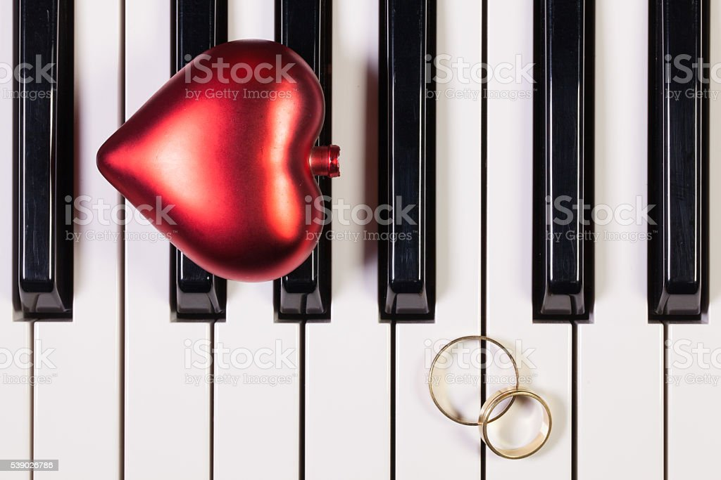 Piano keyboard,red heart and wedding rings stock photo