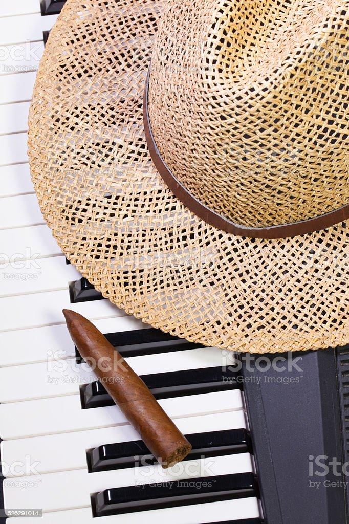 Piano keyboard,straw hat  and luxury cigar stock photo