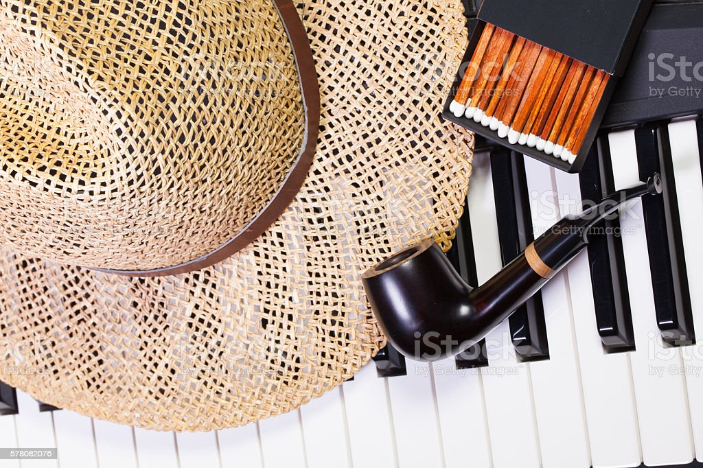Piano keyboard,straw hat  and luxury pipe stock photo