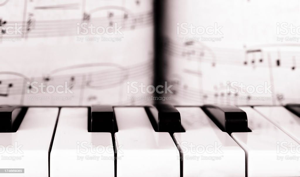 Piano keys in front of the sheet music stock photo