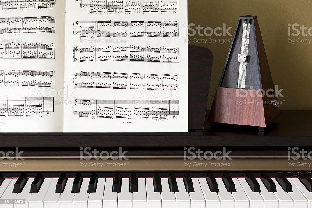 Piano keys sheet music and a metronome stock photo