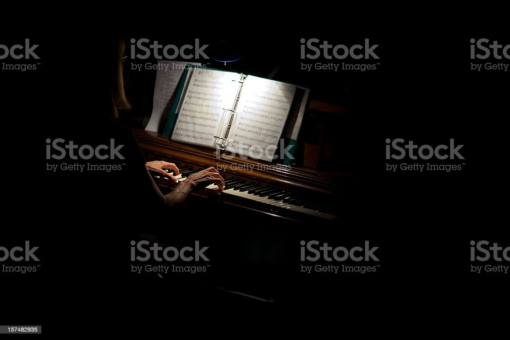 Piano player w/ an ambient light from a small overhead lamp royalty-free stock photo