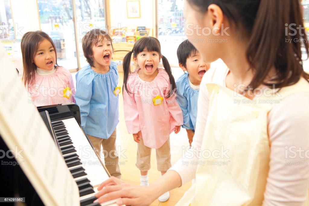 Piano teachers in kindergartens in the kindergarten sing along stock photo