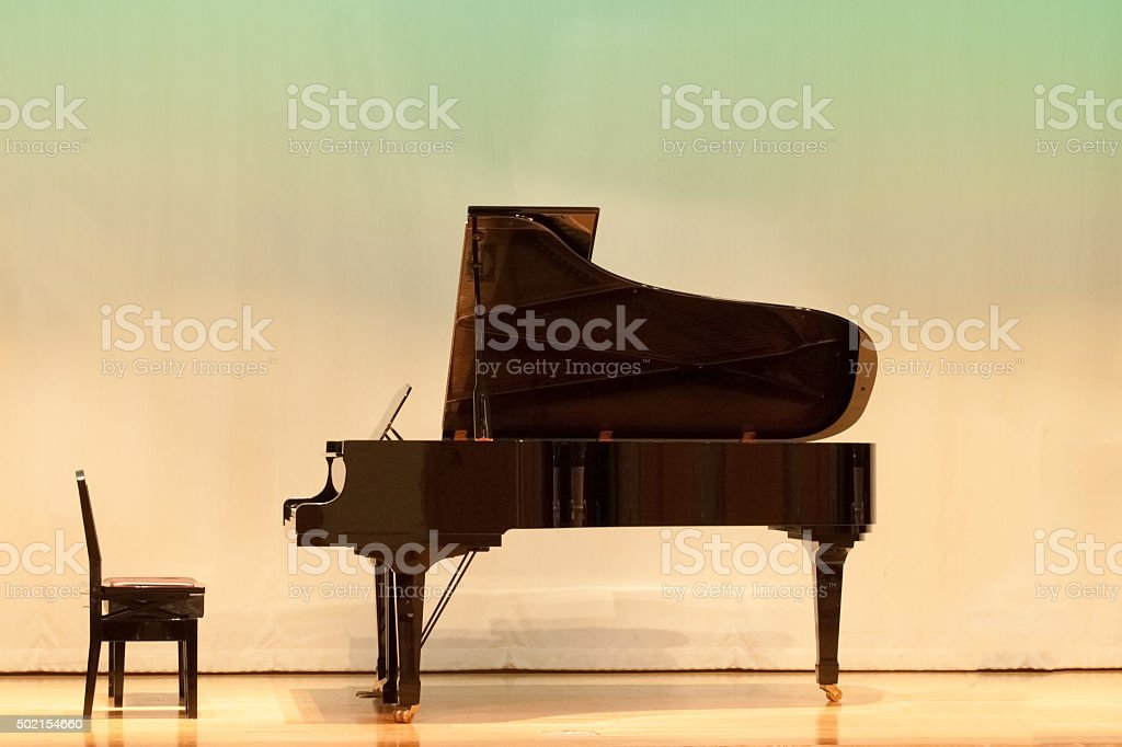 Piano wating for the opening of concert at wooden stage stock photo