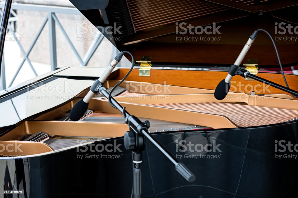 piano with open lid. two microphones above the strings of black grand piano. stock photo