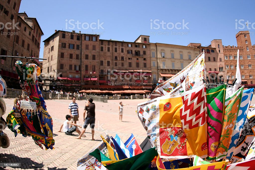 A piazza in Siena, Italy with buildings, people and flags stock photo