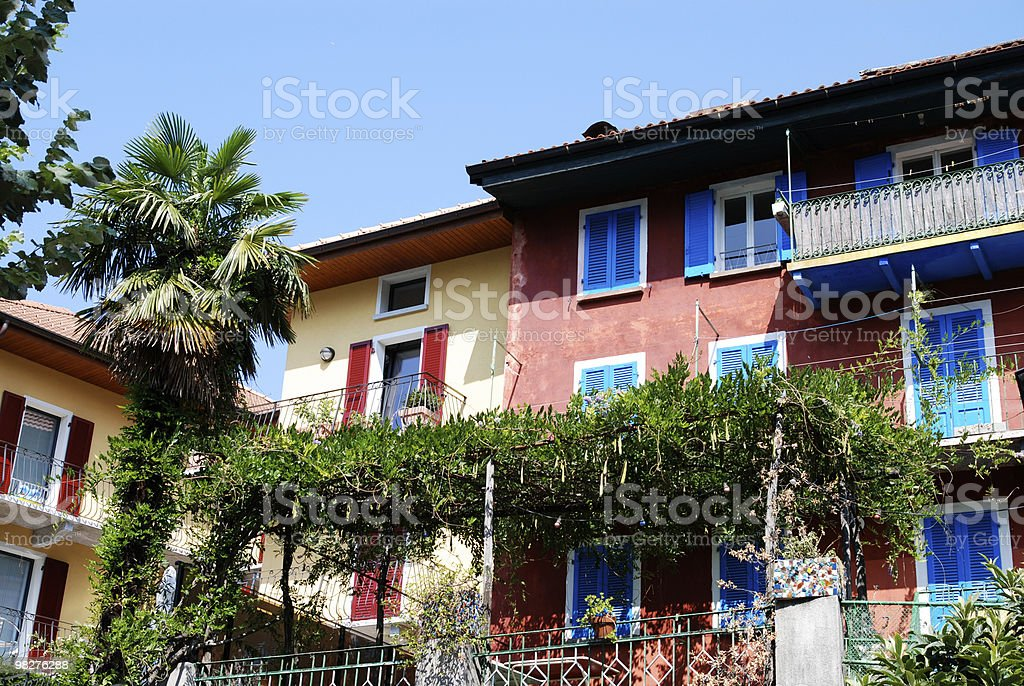 Piazza multicolored houses with palm and wine pergola stock photo