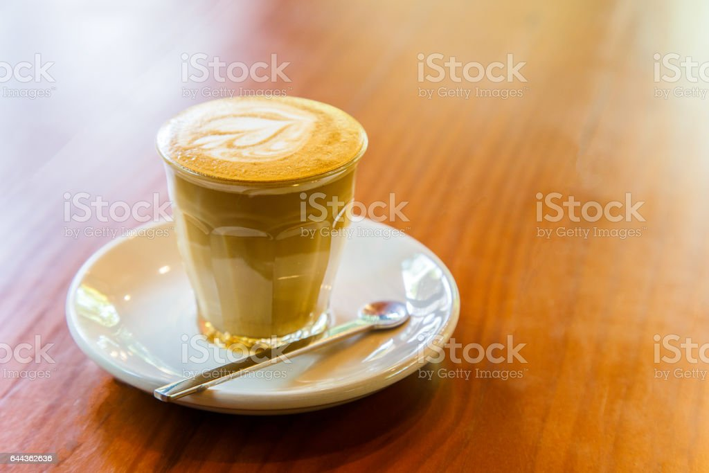 Piccolo latte art in small glass on wooden background stock photo