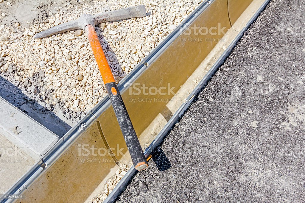 Pick axe on rainwater drainage canal at the building site. stock photo