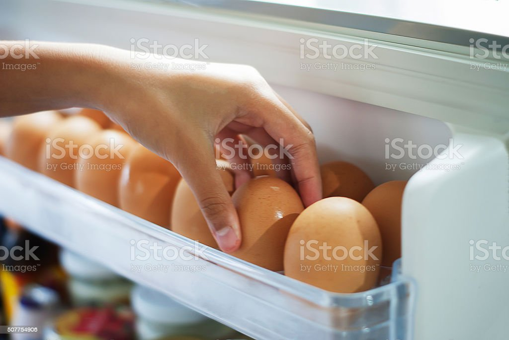 Pick eggs from the refrigerator stock photo