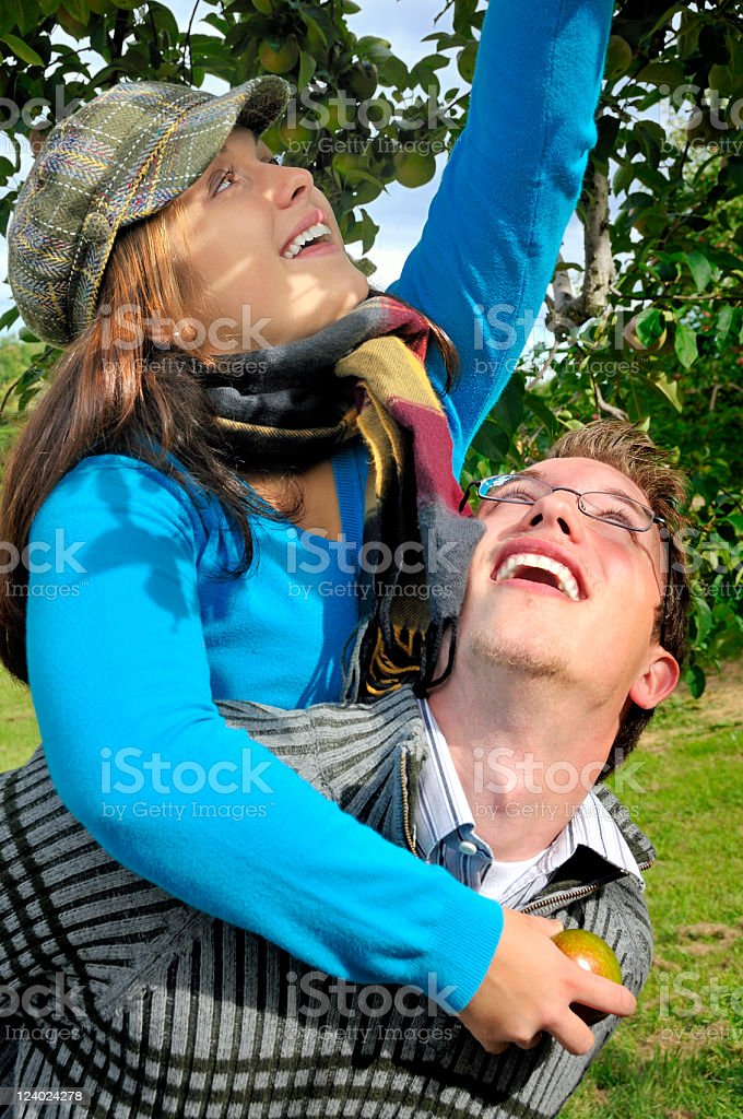 Picking an Apple from Her Boyfriend's Shoulders royalty-free stock photo