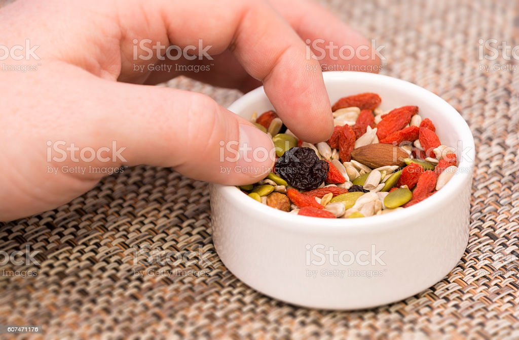 Picking from a nut, seed, goji berry and raisin mix stock photo