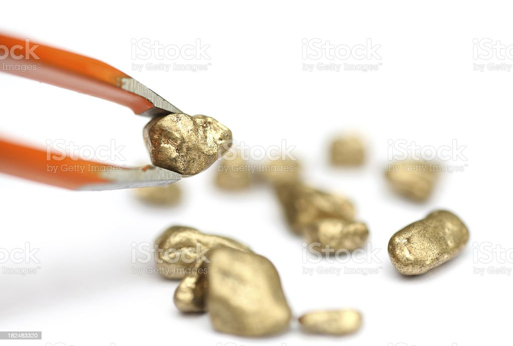 Picking gold with tweezer, isolated royalty-free stock photo