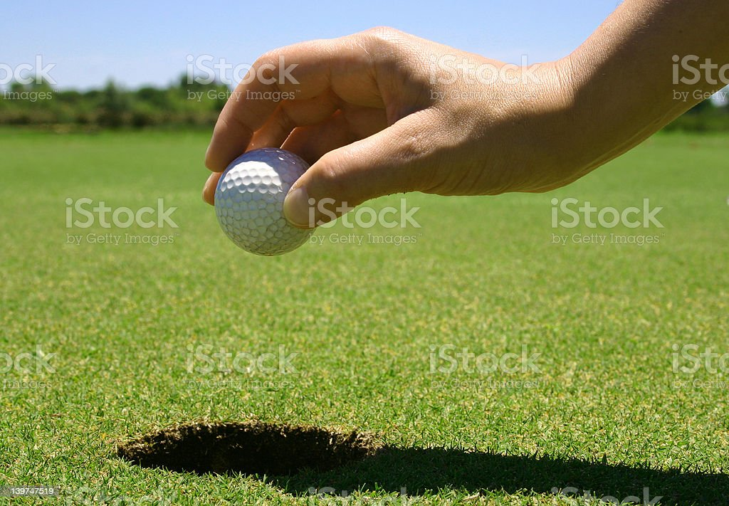 Picking the golf ball from the hole stock photo