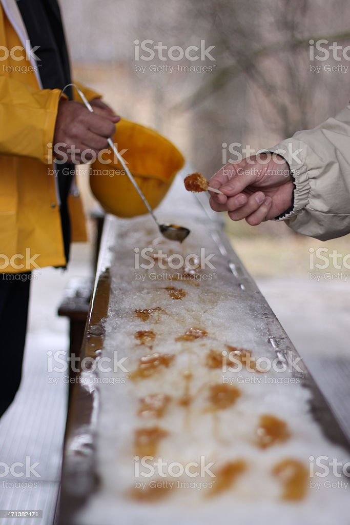 Picking up maple syrup on snow stock photo