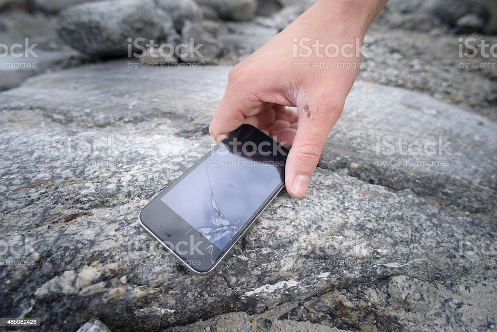 Picking-up Smartphone With Broken Screen on Rock Outdoors stock photo