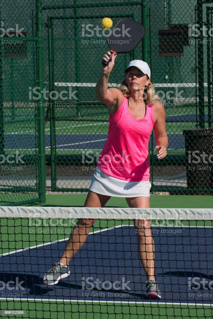Pickleball - Female Player Hitting Overhead Shot at Net stock photo
