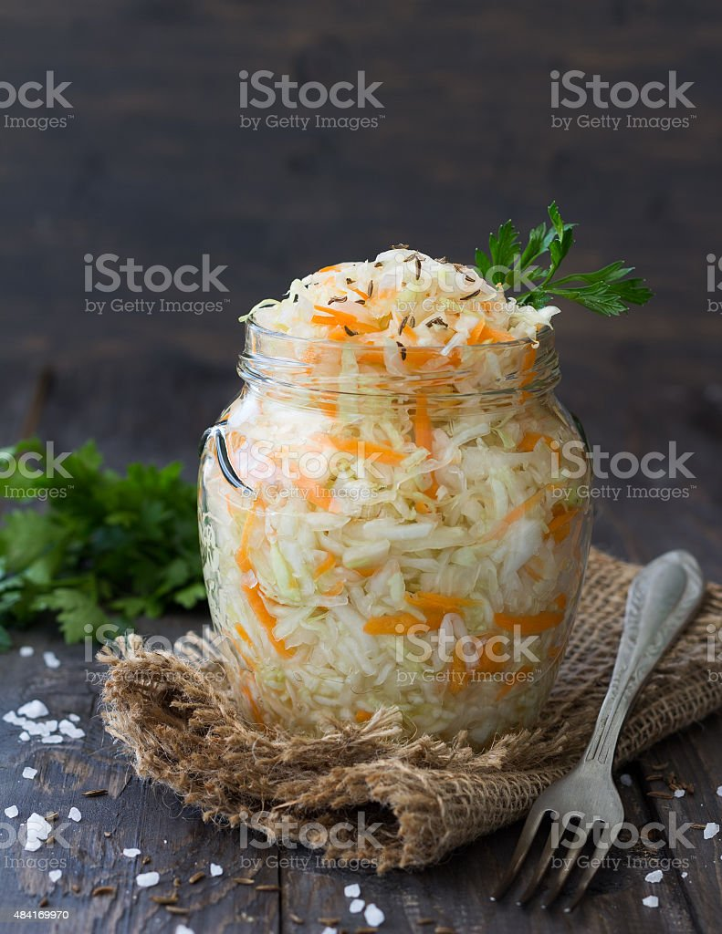 Pickled cabbage with carrots in a glass jar stock photo