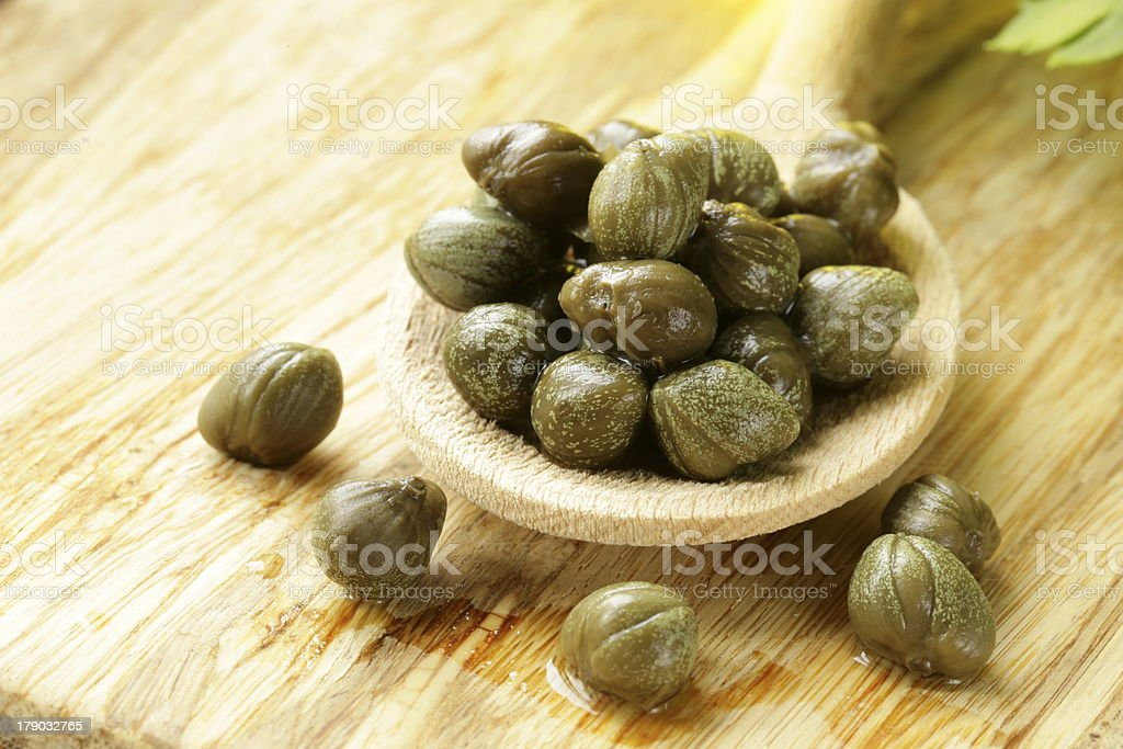 Pickled capers in a wooden spoon stock photo