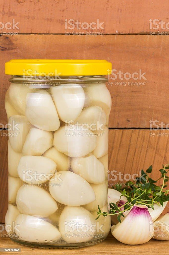 pickled garlic in a jar of green marjoram stock photo