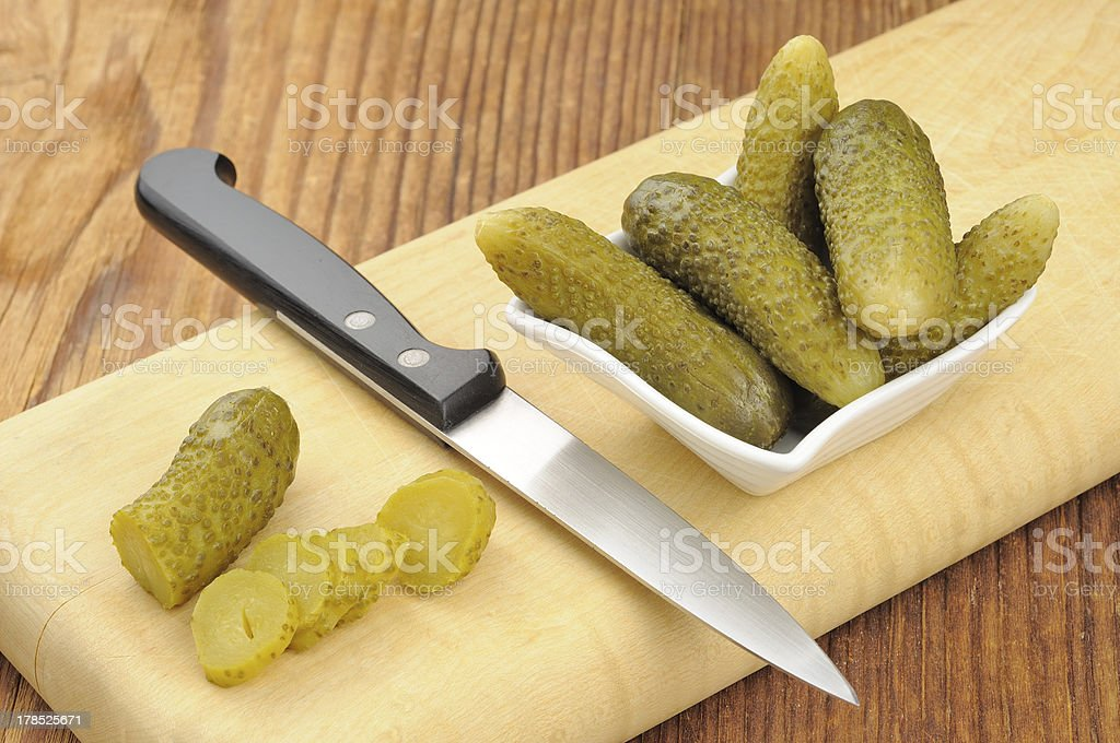 Pickled gherkins on a wooden chopping board stock photo