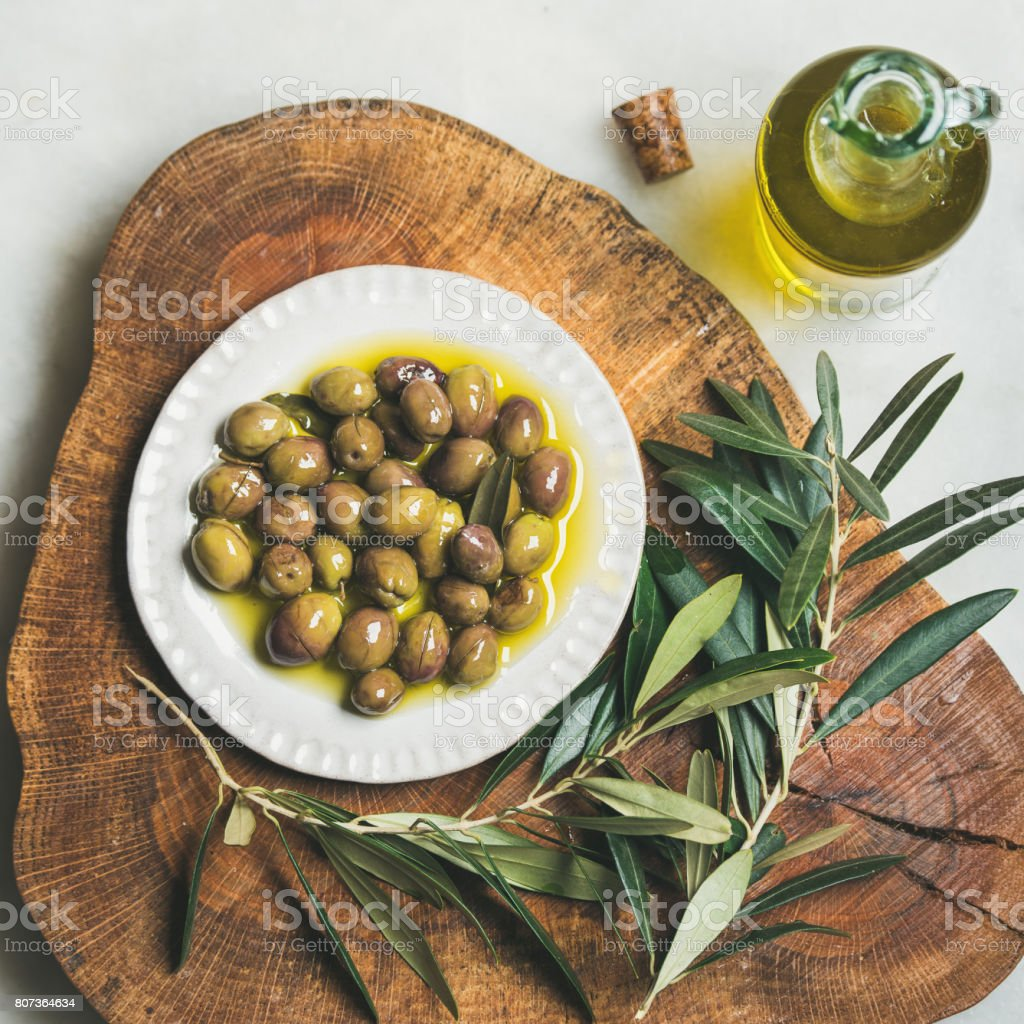 Pickled green Medoterranean olives and olive-tree branch on wooden board stock photo