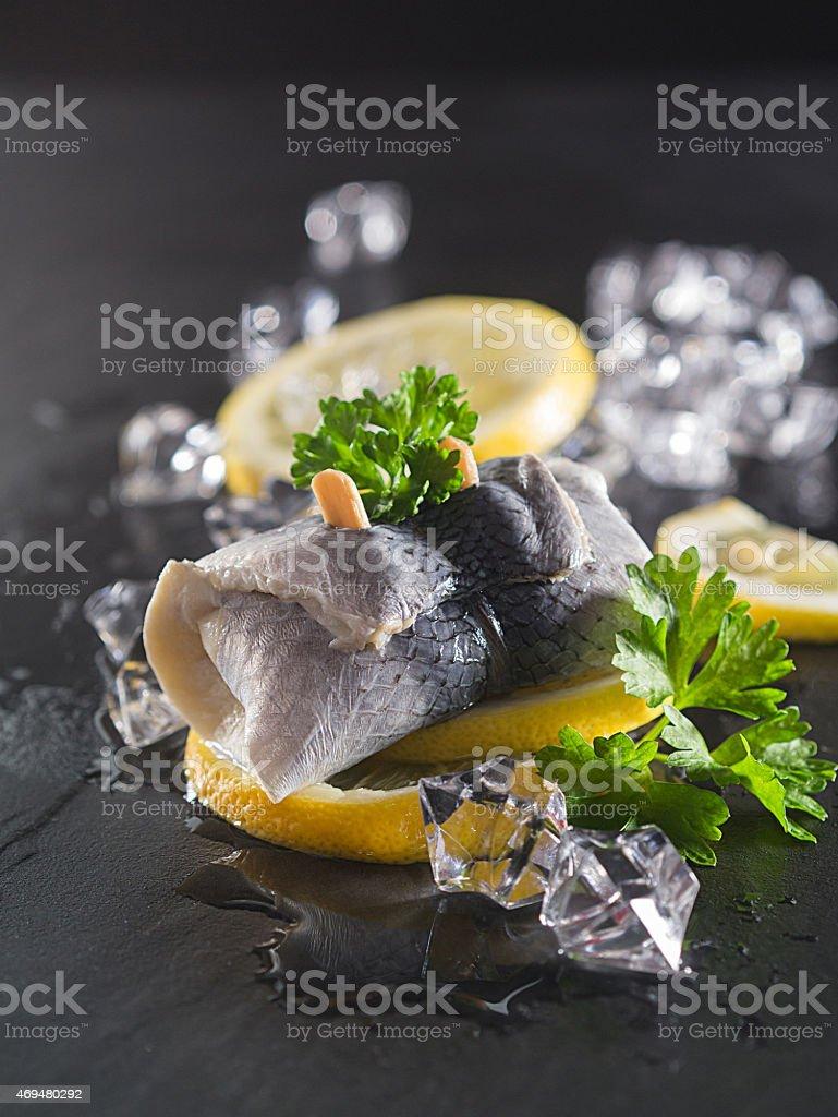 Pickled herring on lemon slices stock photo