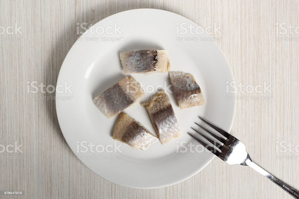 Pickled herring on plate stock photo