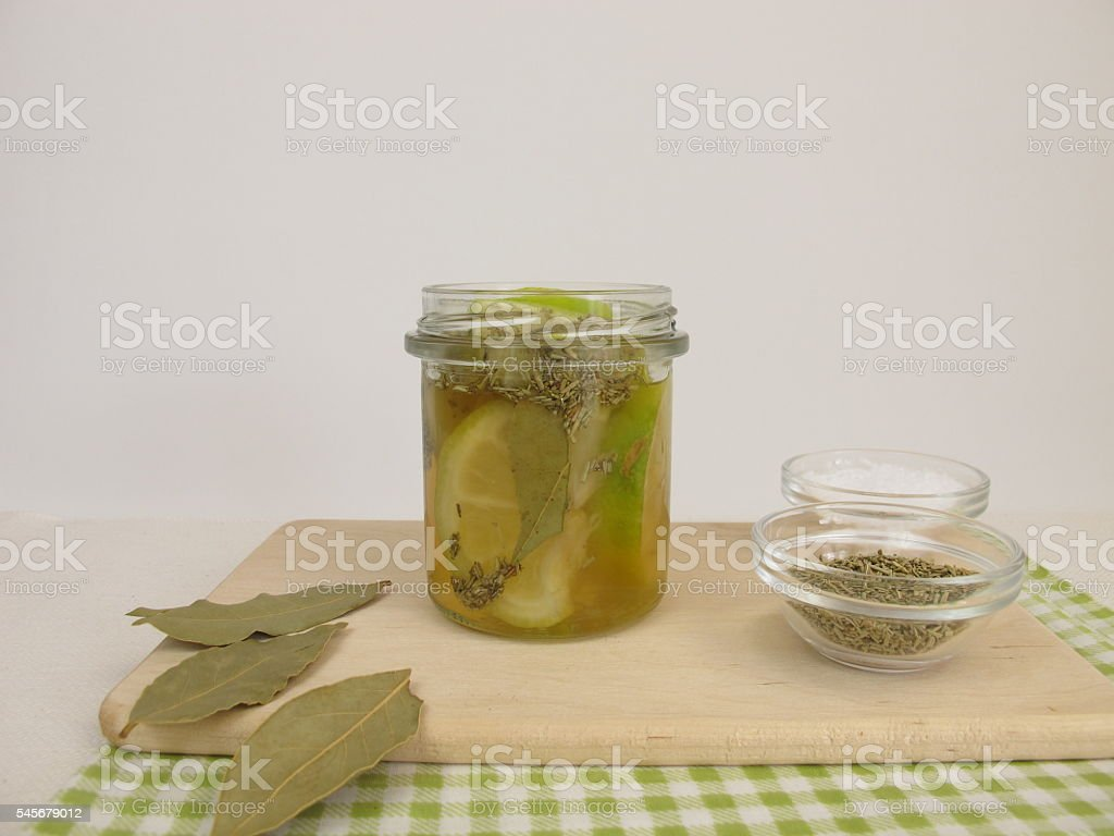 Pickled lemons with rosemary and bay leaves stock photo