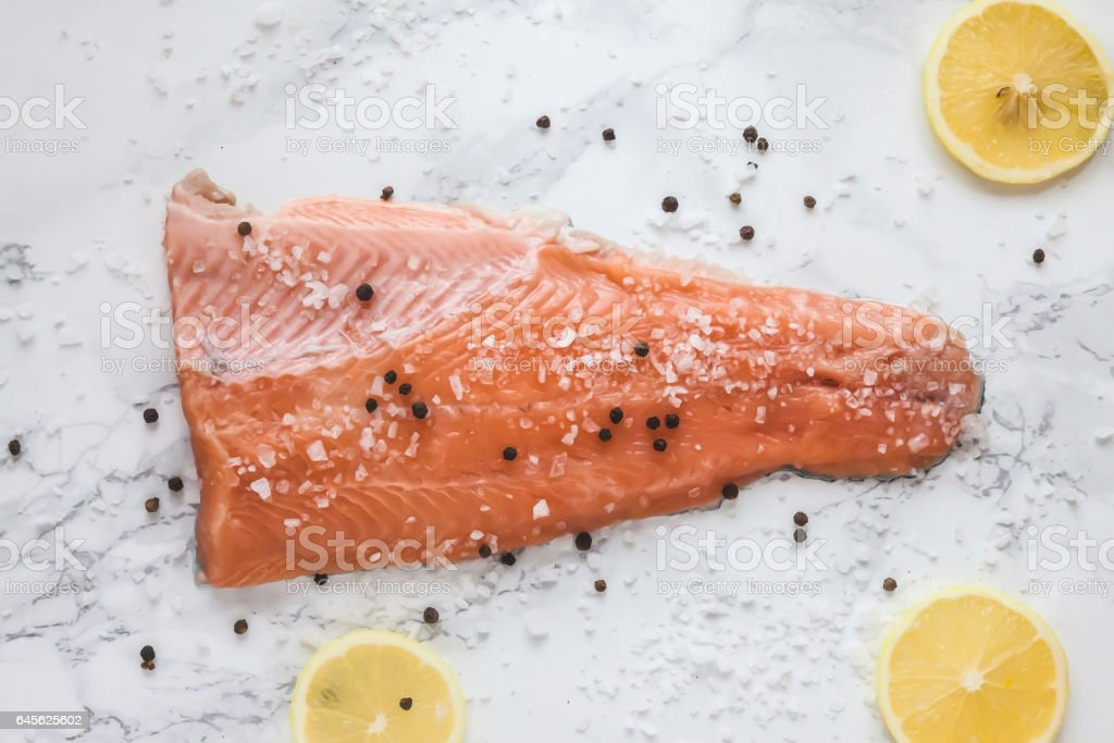 pickled salmon gravlax with pepper and lemon on marble background stock photo
