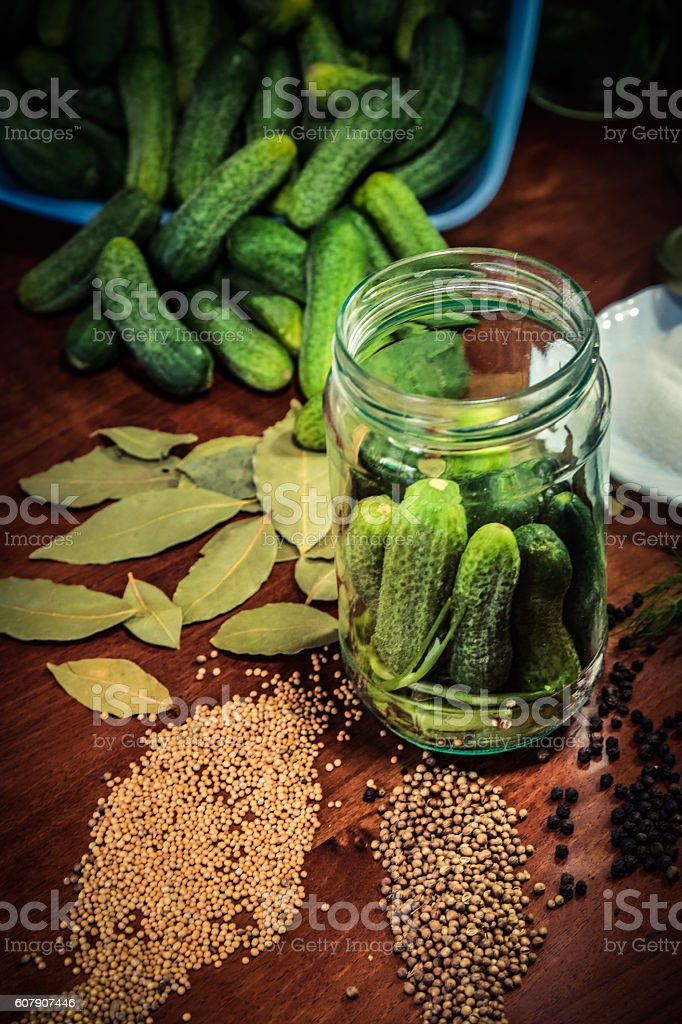 Pickling cucumbers. Jar on table full of ingredients stock photo