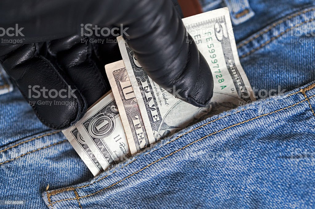 Pickpocket stealing money from pocket. stock photo
