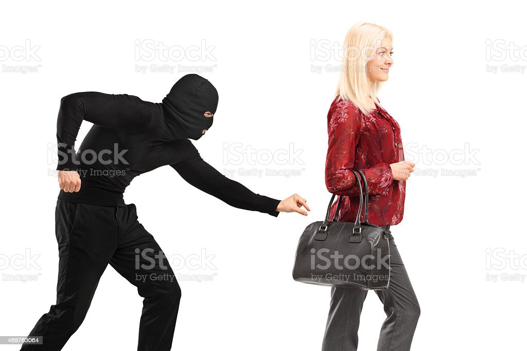 Pickpocket with mask trying to steal from a woman stock photo