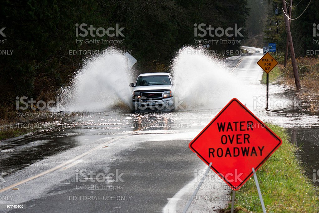 Pickup Truck Splashing Through Flooded Carnation Farm Road stock photo