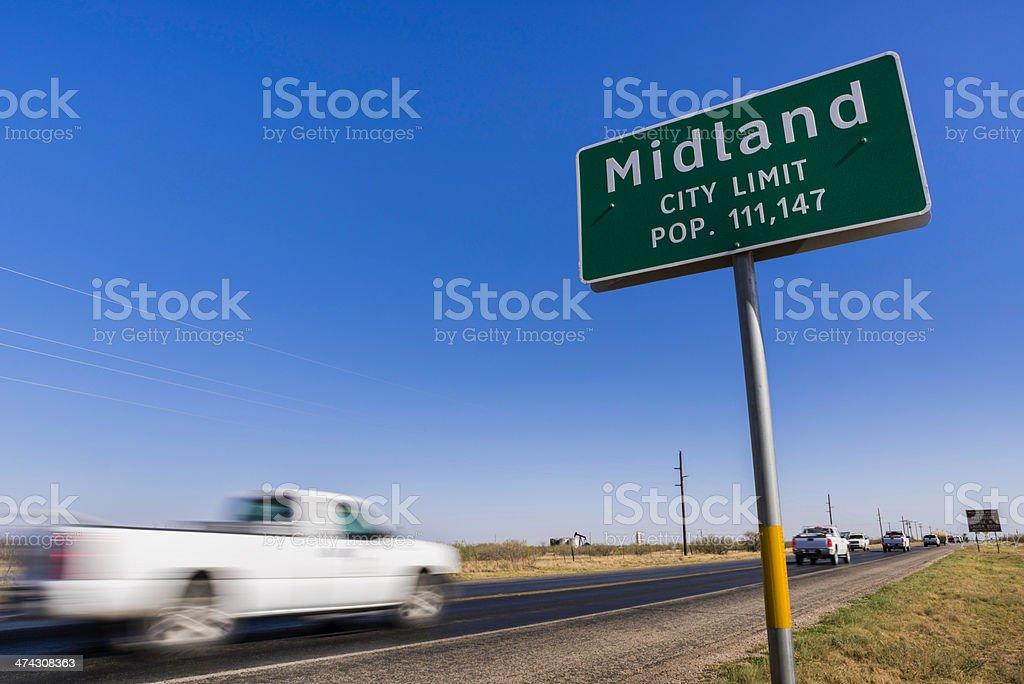 pickup trucks driving on road into Midland Texas royalty-free stock photo