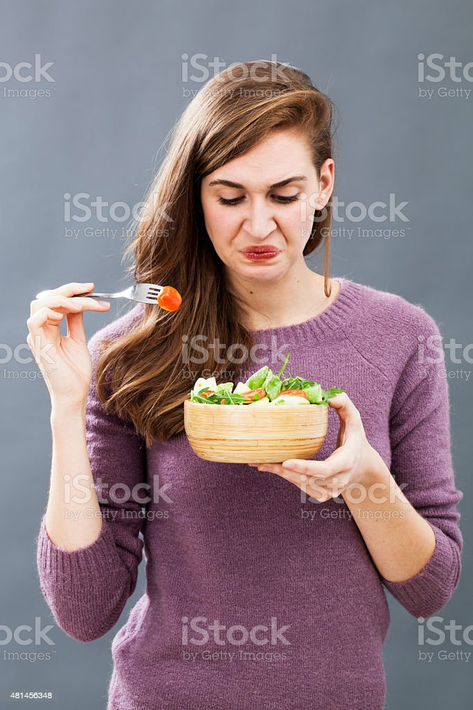 picky 20s woman developing aversion in eating raw vegetables stock photo