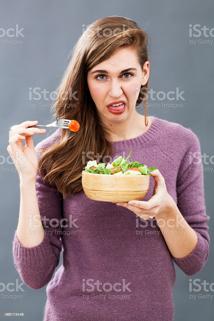 picky 20s woman disgusted in eating a mixed green salad stock photo
