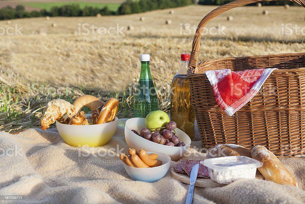 Picnic basket and different food, drinks on straw field royalty-free stock photo