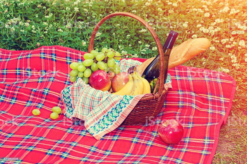Picnic basket on the blanket stock photo